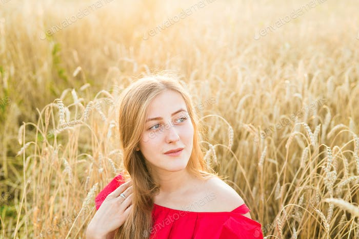Beautiful lady in wheat field at sunset