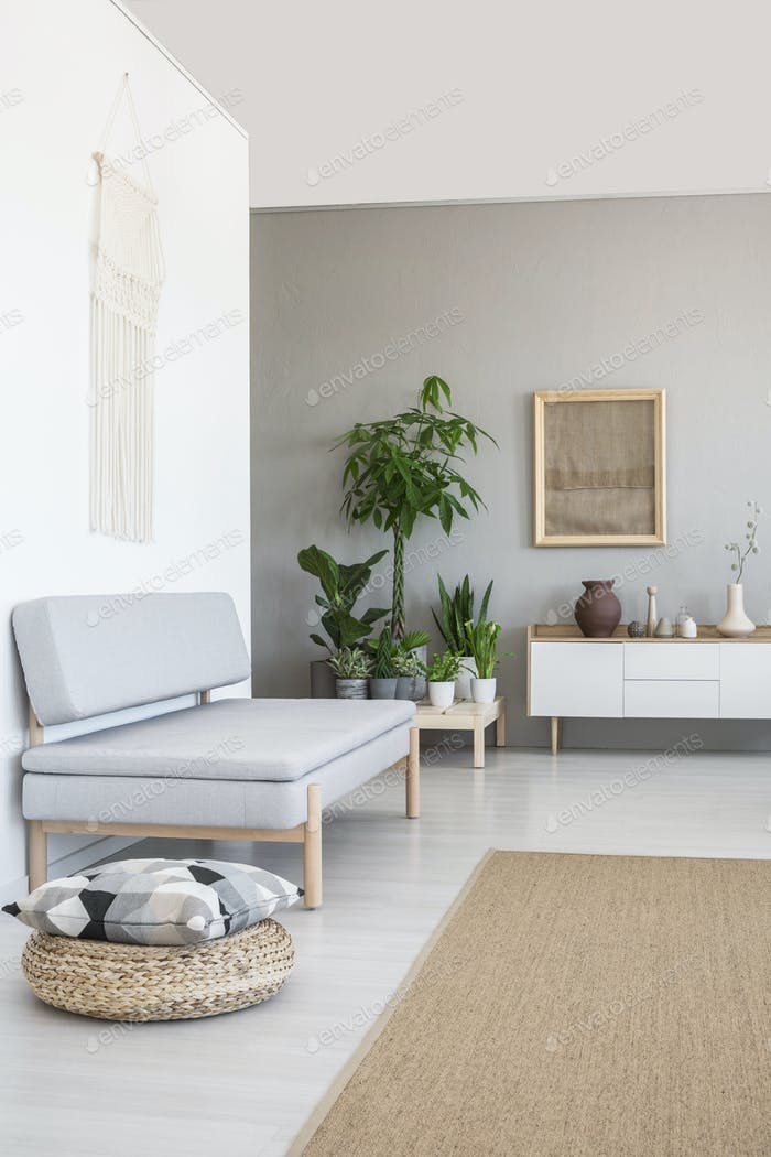 Pillow on pouf next to grey couch in scandi living room interior