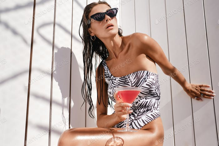 Gorgeous stylish brunette girl in one-piece swimsuit and sunglasses with cocktail sensually posing