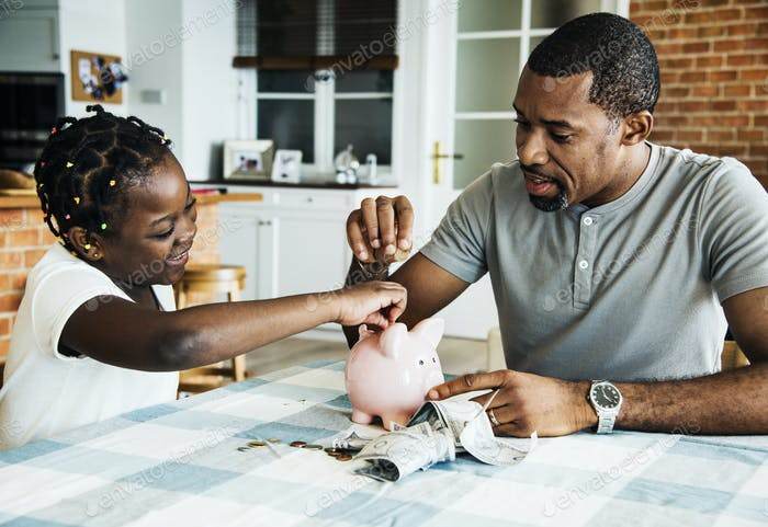 Papá y la hija ahorran dinero a la alcancía