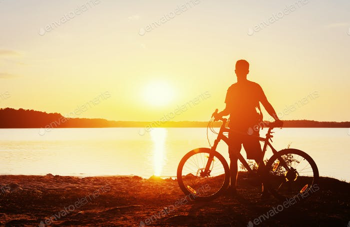 Junge auf dem Fahrrad bei Sonnenuntergang