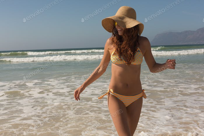 Front view of beautiful young Caucasian woman in bikini and hat walking on the beach. She is smiling