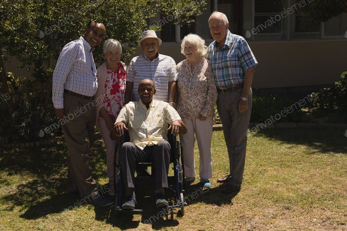 Happy senior friends standing with one disabled looking at camera in garden on sunny day