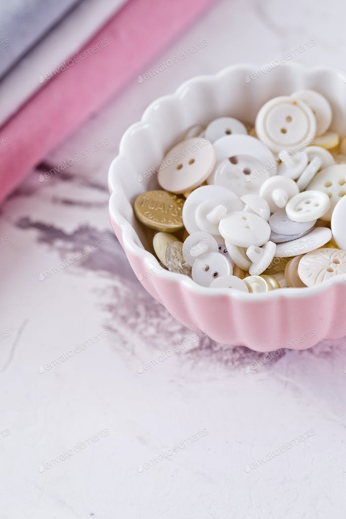 stack of fabrics and buttons over marble table