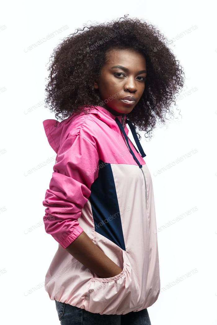 Saucy young curly brown-haired girl dressed in the pink sport jacket stands at the white background