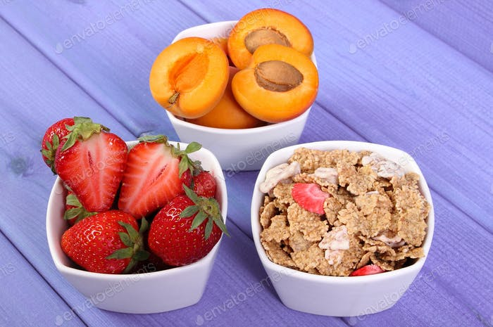 Fresh fruits, wheat and rye flakes in bowl on boards, concept of healthy lifestyle and nutrition
