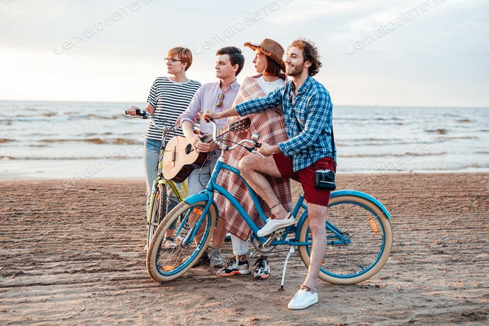 Four friends on the beach with their bicycles