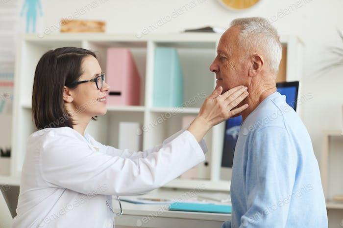 Lächelnder Arzt Untersuchung Senior Man in der Klinik