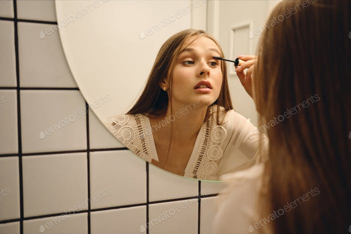 Young attractive girl in white dress standing near mirror thoughtfully applying mascara in bathroom