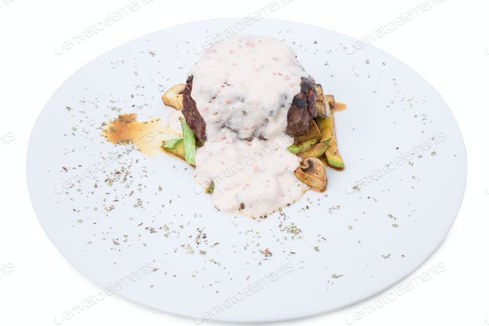 Grilled beef steak with vegetable garnish.