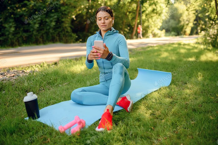 Fit training on mat in park, woman in headphones