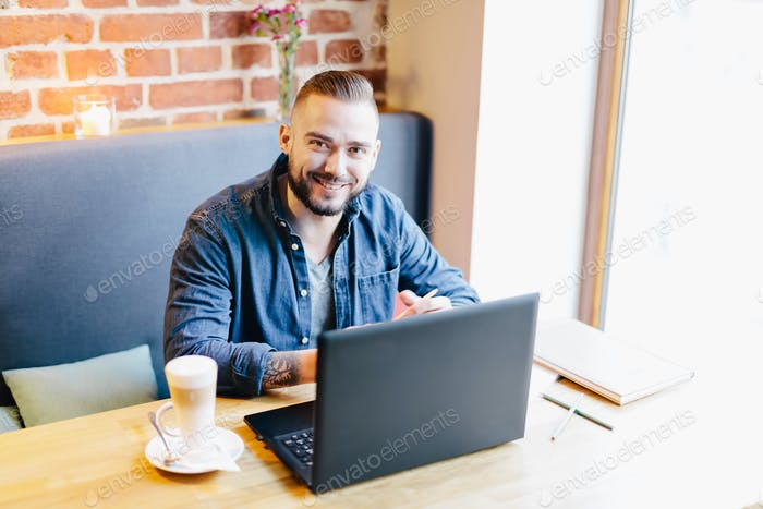 Attractive man smiling in a cafe. Working environment.