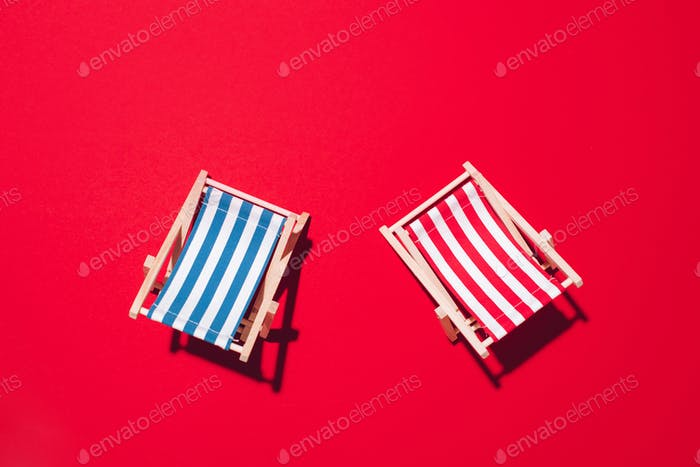 Two deck chairs with hard shadow on red paper background. Flat lay and copy space. Summer travel