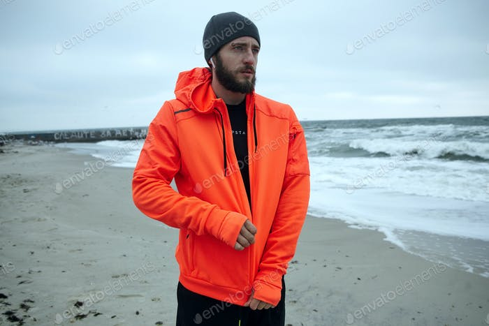 male looking thoughtfully ahaead while fastening zipper on his orange sporty hoodie