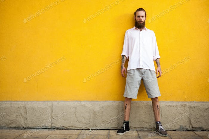 Cool Tattooed bearded hipster on yellow wall