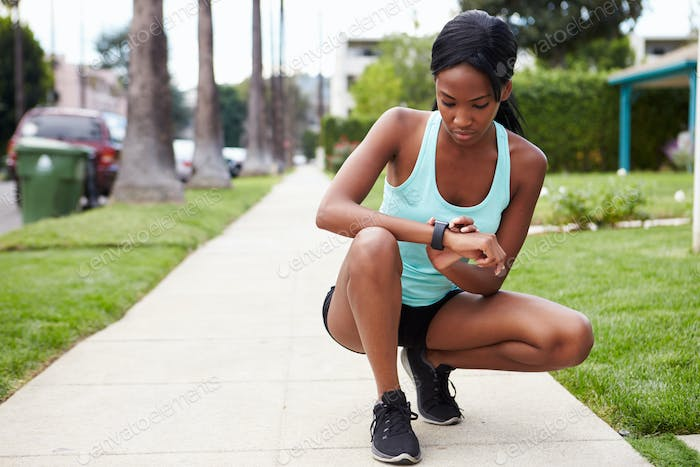Young woman checking smart watch in the street before a run