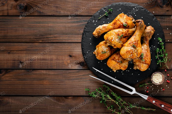 Grilled chicken legs on wooden background. Top view