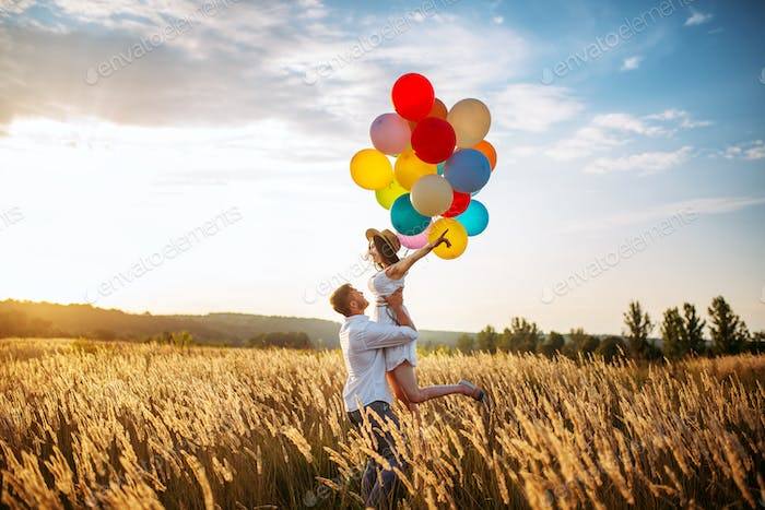 Husband hugs wife with balloons in wheat field