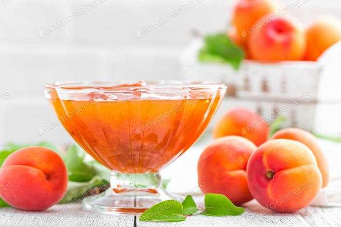 Apricot jam and fresh fruits with leaves on white wooden table