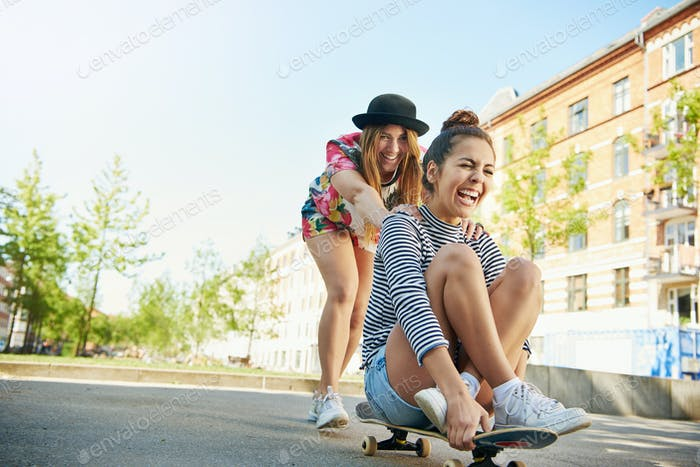 Excited teen woman pushing friend on skateboard