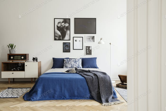 Blanket on blue bed with pillows in retro bedroom interior with