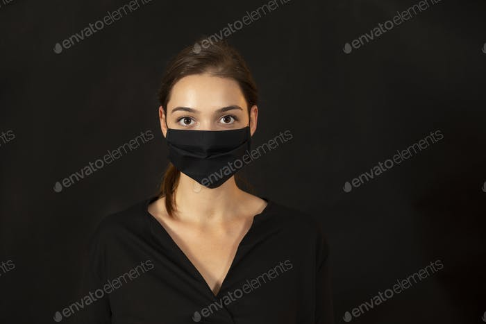 Studio portrait of a young woman wearing a face mask on dark background
