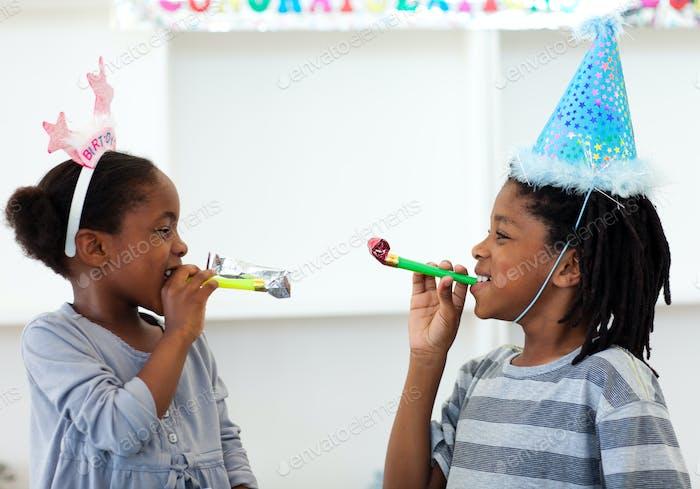 Happy siblings having fun at a birthday party
