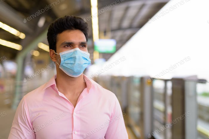 Young Indian businessman wearing mask and waiting with distance at the skytrain station