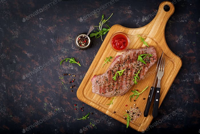 Saftiges Steak seltenes Rindfleisch mit Gewürzen auf einem Holzbrett. Draufsicht. Flache Lag.