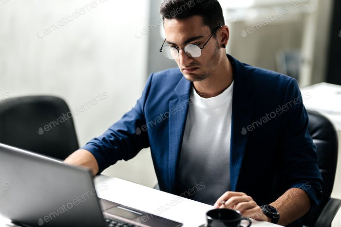Dark-haired young architect in glasses dressed in blue checkered jacket works on the laptop in the