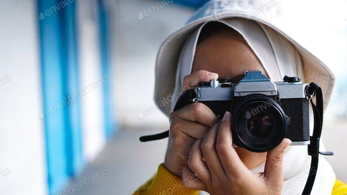 an Asian woman traveler in keraton solo wearing jilbab and analog camera
