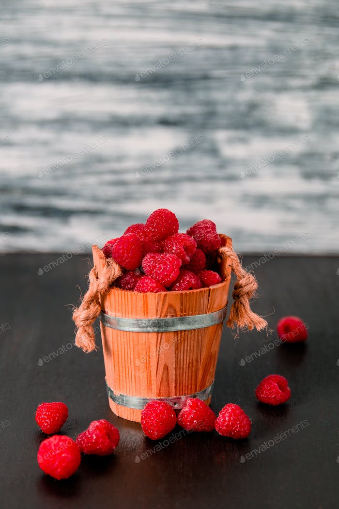 Red raspberries in a basket on black wooden background. Close up.
