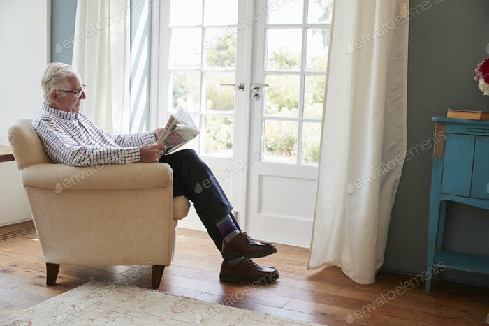Senior man sitting in an armchair reading newspaper at home