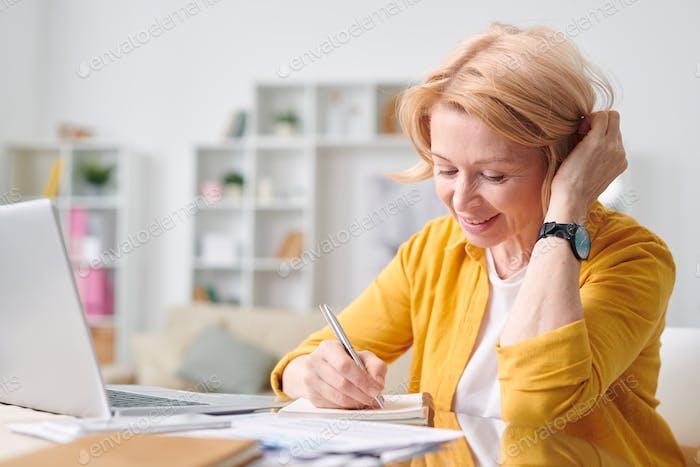 Hübsche blonde Geschäftsfrau in Freizeitbekleidung Planung Arbeit oder Notizen machen