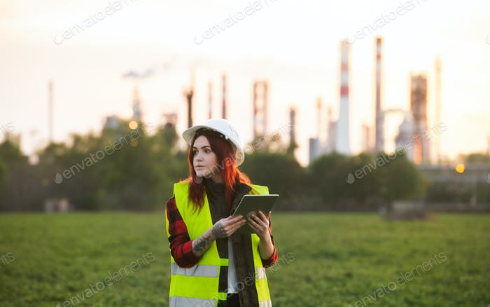 Young woman engineer with tablet standing outdoors by oil refinery. Copy space
