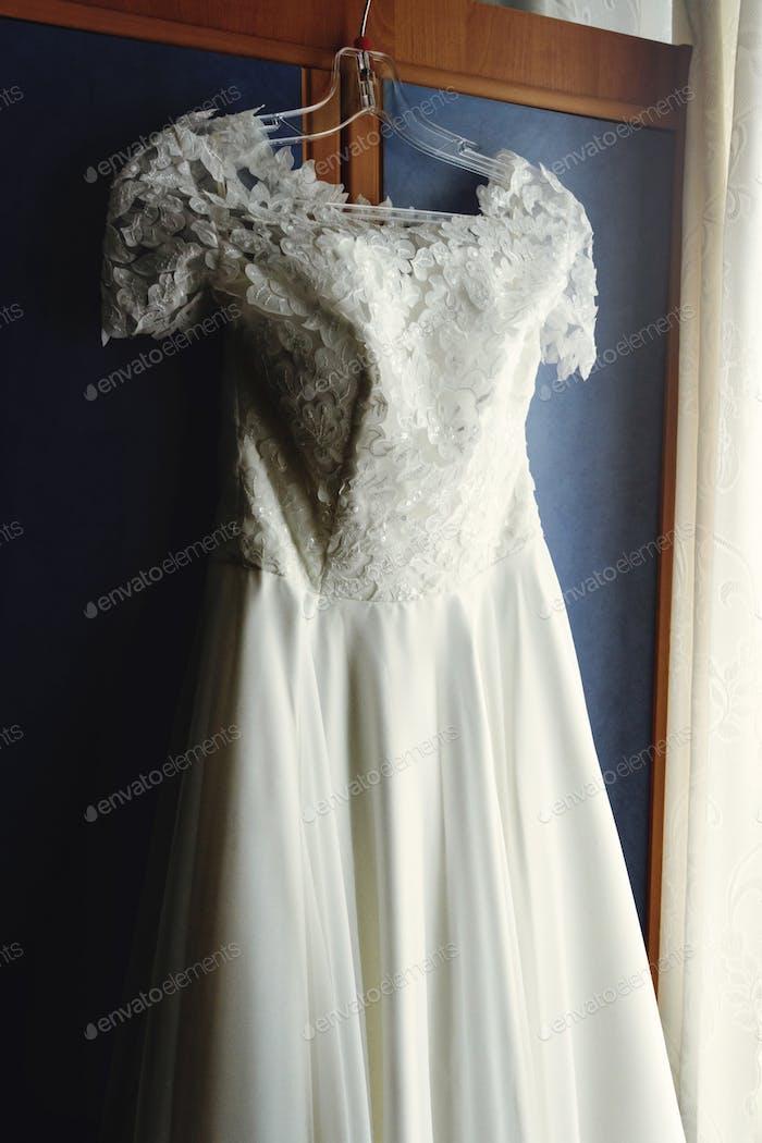 beautiful white luxury wedding dress on hanger on the background of a window