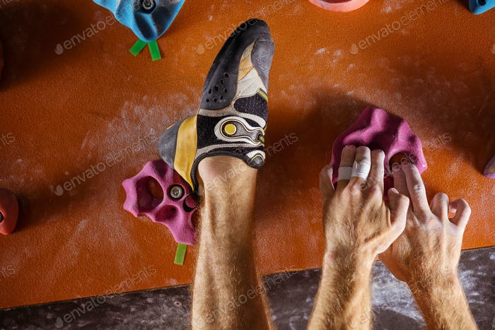 Closeup of rock climber's hands and foot on holds in indoor climbing gym
