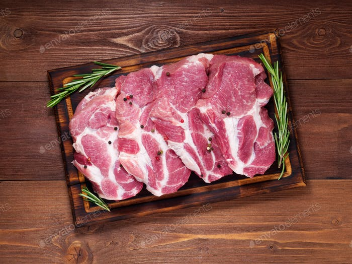 Raw Pork Loin chops on a cutting board with herbs rosemary on dark wooden background, top view