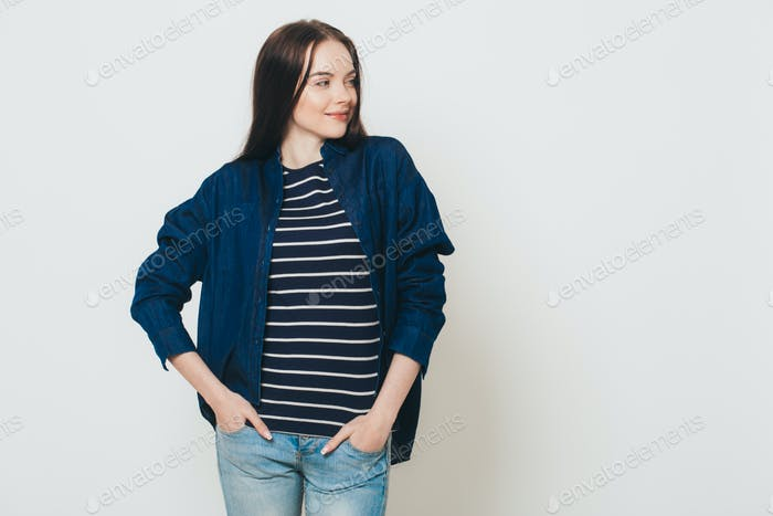 Portrait of a beautiful european woman in jeans and a striped blouse on a gray wall background