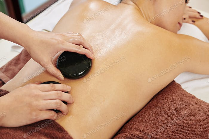 Woman massaging clients back with stones