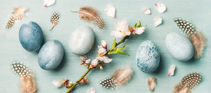 Painted eggs for Easter, feathers, blooming almond flowers, wide composition