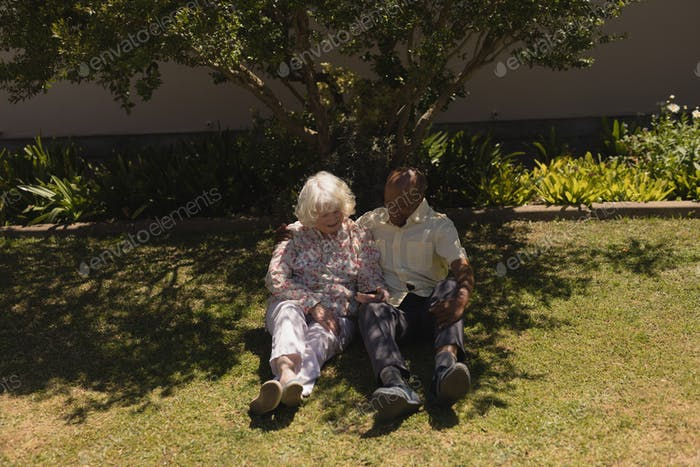 Front view of happy senior couple using mobile phone and sitting on the grass in garden