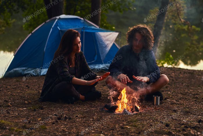 Young hipster couple hiking in the forest warming near a campfire at camp.