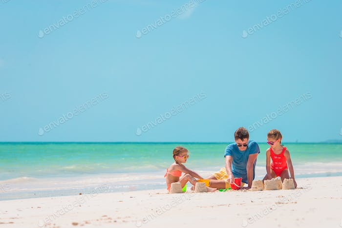 Father and kids making sand castle at tropical beach. Family playing with beach toys