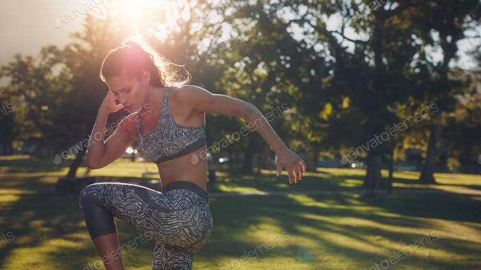 Fitness woman warming up at the park on a sunny day