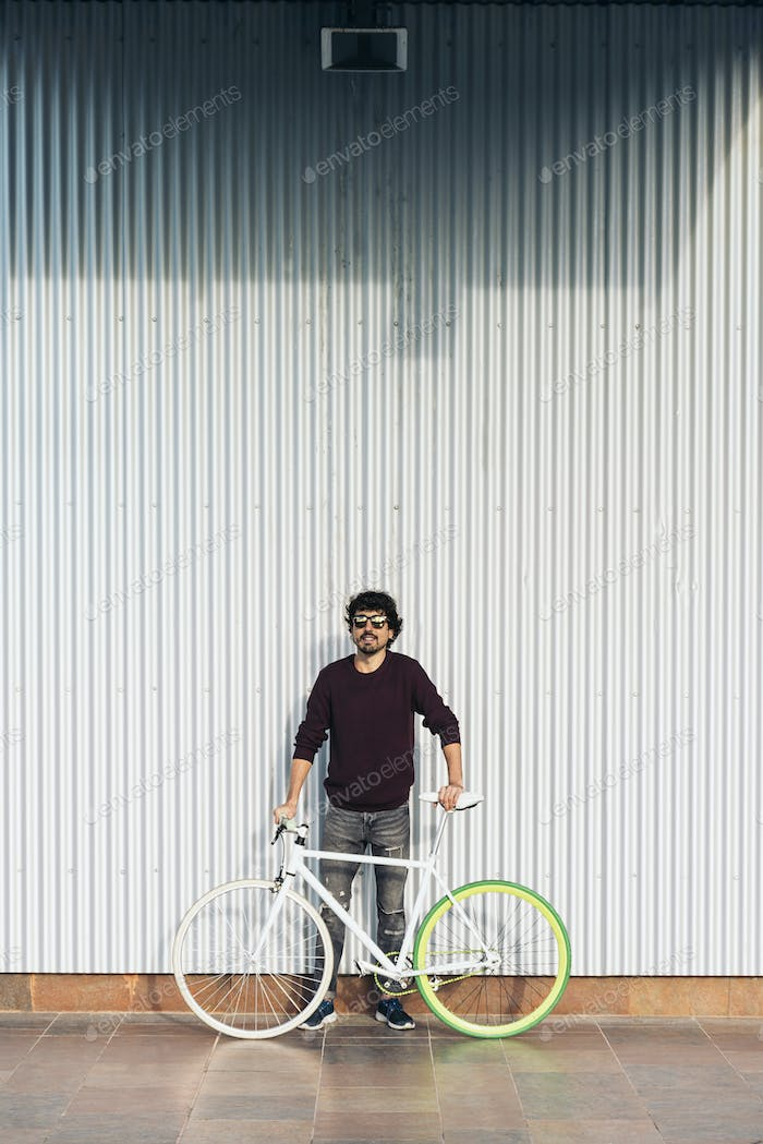 Handsome young man with fixed gear bicycle in the street