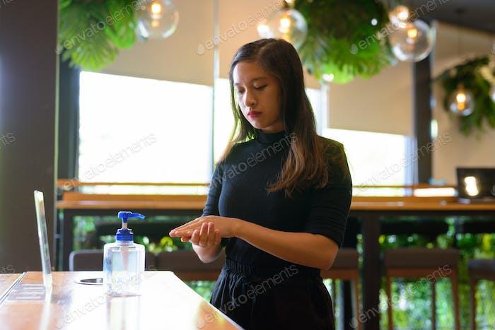 Junge schöne asiatische Geschäftsfrau mit Handdesinfektionsmittel als richtige Hygiene Etikette am Kaffee