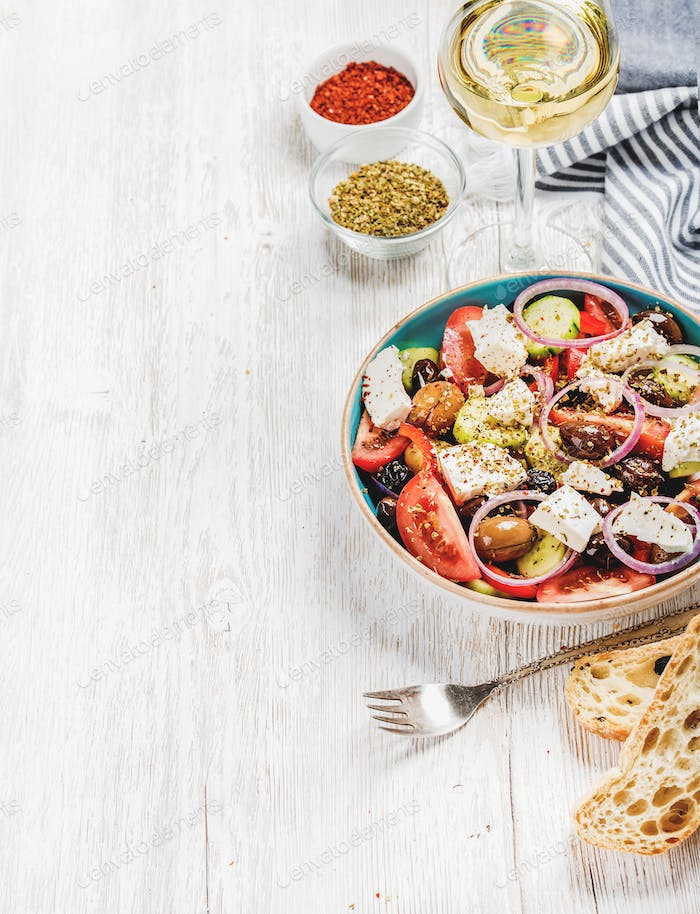 Greek salad with bread, herbs and glass of white wine