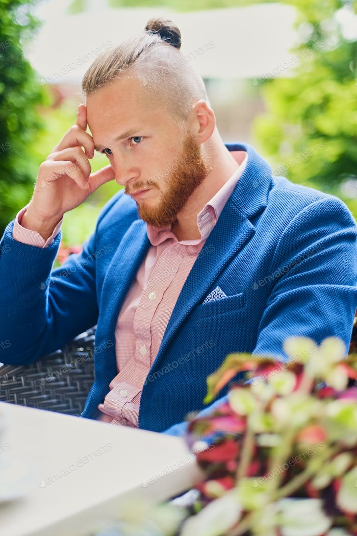 Redhead male in a blue jacket at the table in a cafe.