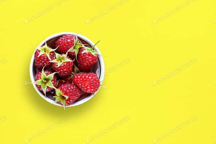Raspberry in bowl on yellow table